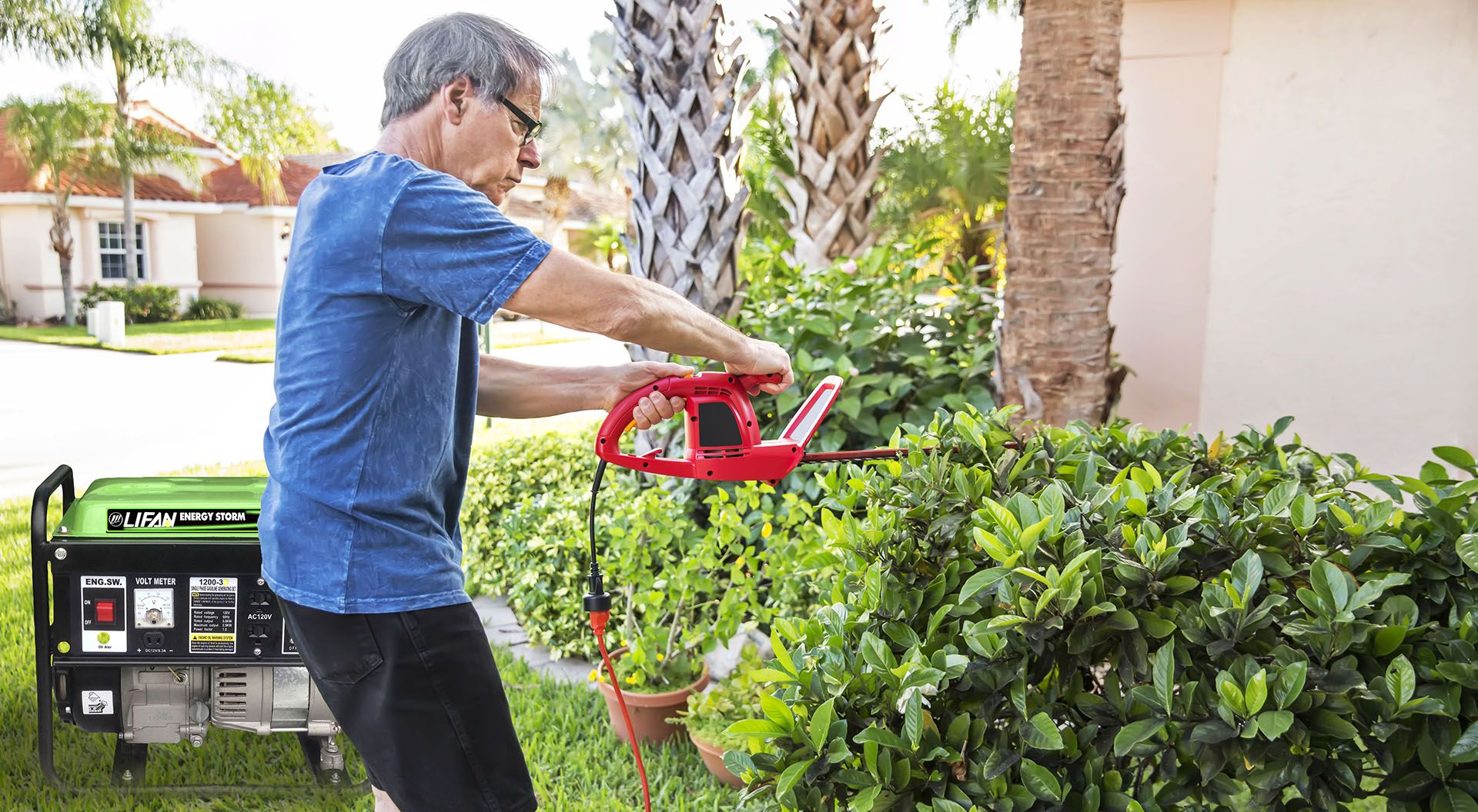Senior caucasian man trims the hedges outside his home